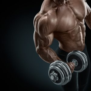 Closeup of a handsome power athletic guy male bodybuilder doing exercises with dumbbell. Fitness muscular body on dark background. muscle building